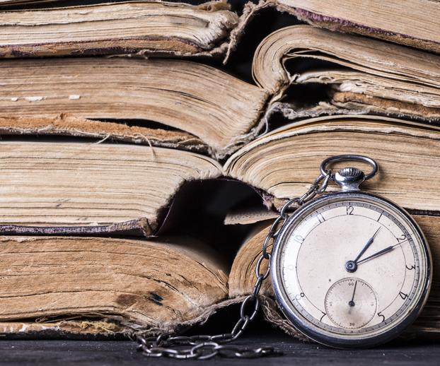 livres anciens avec une montre à gousset pour illustrer la notoriété et l'historique d'une société