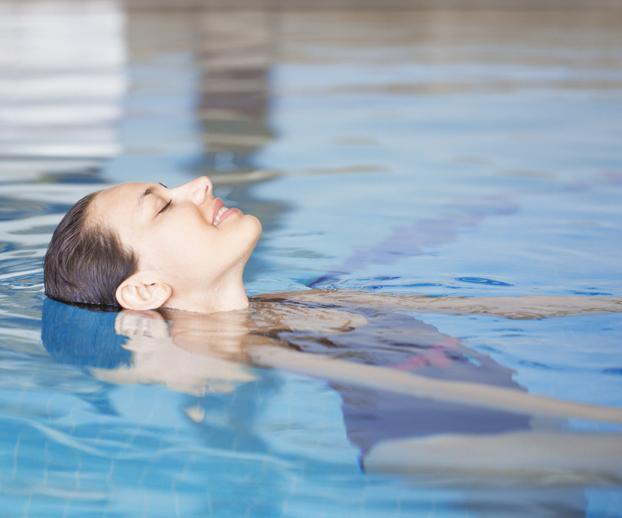 Jeune femme se détendant dans une piscine profitant d'un moment de détente et de bien être
