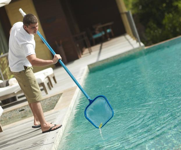Jeune homme réalisant l'entretien d'une piscine à l'aide d'une épuisette