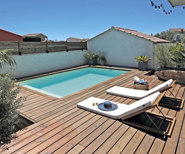 Piscine intégrée dans un jardin avec terrasse en bois