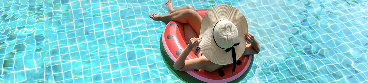 Jeune femme assise sur une bouée dans une piscine.
