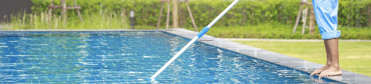 homme procédant au nettoyage de sa piscine au moyen d'un balai spécial piscine