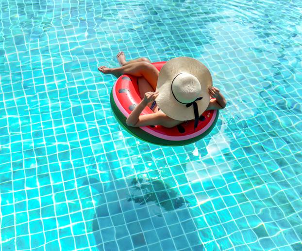 Jeune femme assises sur une bouée et se détendant dans une piscine servant d'illustration à la partie sur la remise en route en début de saison du bassin