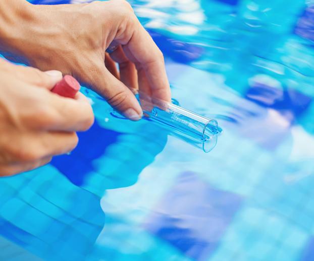 Main avec une éprouvette contenant un échantillon de l'eau pour faire différentes mesures dans le but de traiter l'eau de la piscine