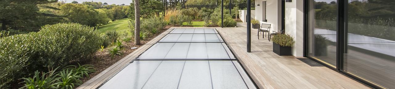 Piscine attenante à une maison d'architecte et comportant un abris bas recouvrant la piscine pour sécuriser le bassin