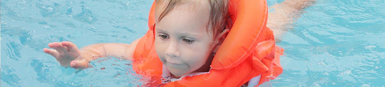 petit enfant avec des brassards dans une piscine