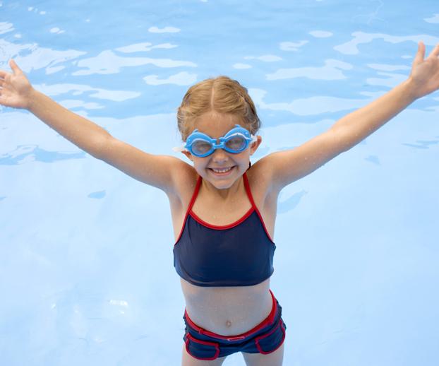jeune enfant levant les bras et installée dans une piscine