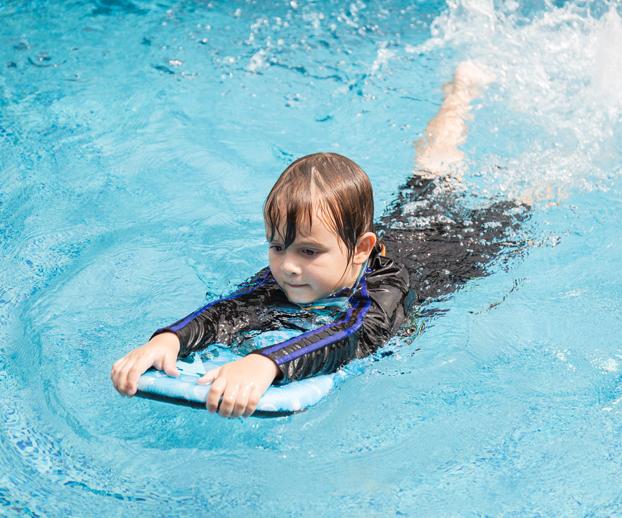 Jeune garçon apprenant à nager dans une piscine