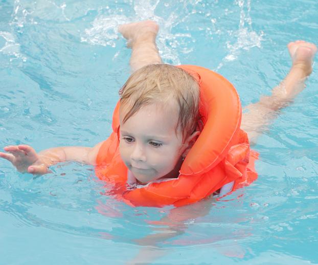 Jeune enfant nageant dans une piscine avec des brassards de sécurité