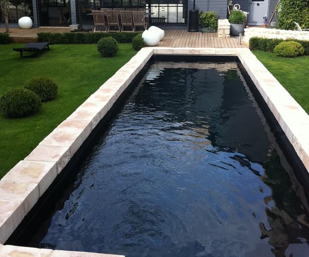Magnifique piscine avec un revêtement foncé et donnant un nouvel aspect esthétique à la piscine