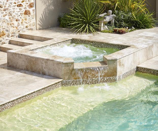 magnifique spa d'extérieur en pierre installé dans un jardin et surplombant une piscine