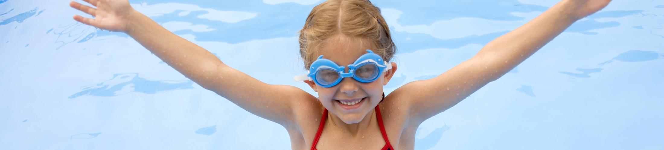 Petite fille souriant avec des lunettes de piscine