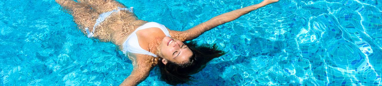 Jeune femme se baignant dans une piscine en position allongée pour se relaxer