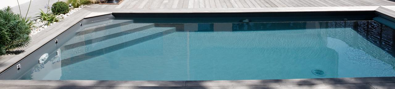 Magnifique piscine avec plage en bois illustrant les plages et margelles des piscines
