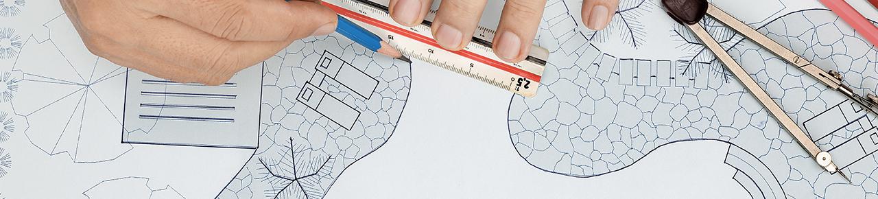 main et outils de dessin d'architecture avec un dessin et maquette en fond illustrant la rfelxion et les dessins qui sont faits en amont lors de la conception de sa piscine