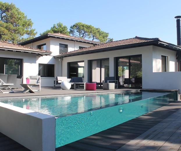 Magnifique piscine avec parois en verre et en fond la maison