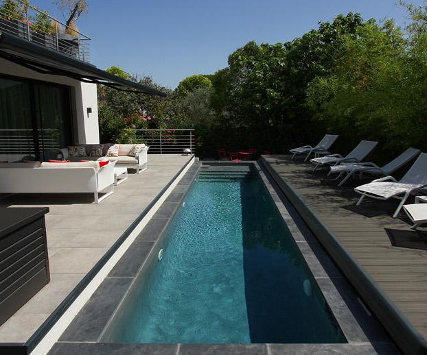 piscine avec un couloir de nage avec en fond paysager un grand jardin