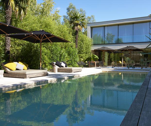 Magnifique piscine parfaitement intégrée dans un jardin verdoyant avec une maison moderne et montant bien l'intégration de la piscine à son environnement direct