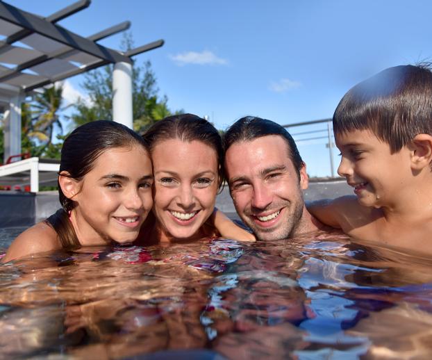 Une famille sourit en se baignant dans sa piscine familiale