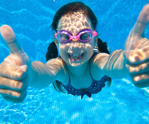 petite fille dans une piscine qui signale que tout va bien et servant d'illustration à l'idée reçue numéro 2 qui est que la piscine consomme beaucoup d'eau