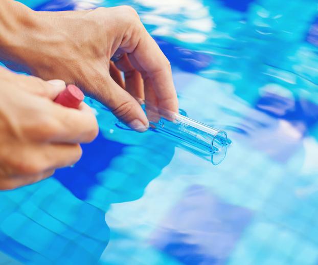 Mains réalisant des analyses de l'eau pour réaliser l'entretien de la piscine - équilibre de l'eau