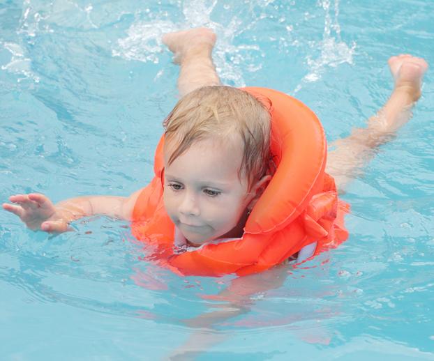Enfant nageant dans une piscine avec un gilet illustrant la sécurité des piscines dans les locations saisonnières