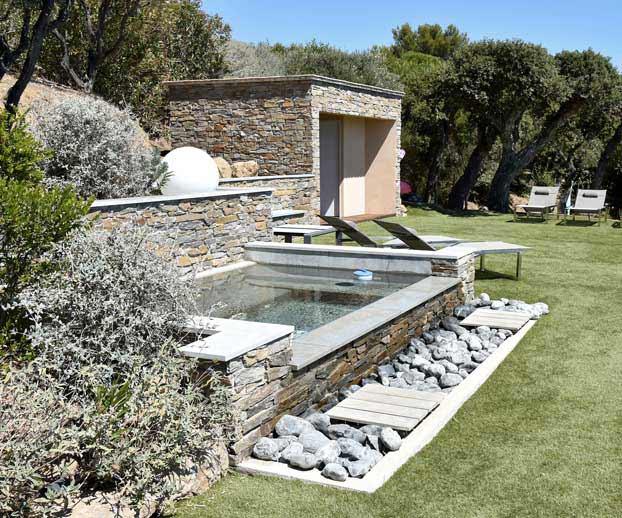 joli spa avec en fond de paysage une maison rénovée en pierres anciennes