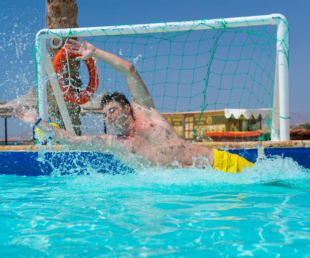 jeune homme plongeant devant un but de waterpolo dans une piscine