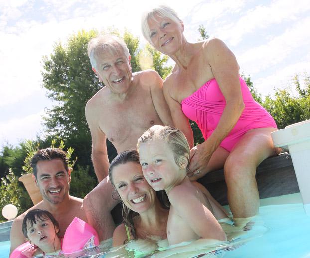 Une image montrant une famille des grands parents aux petits enfnats dans une piscine