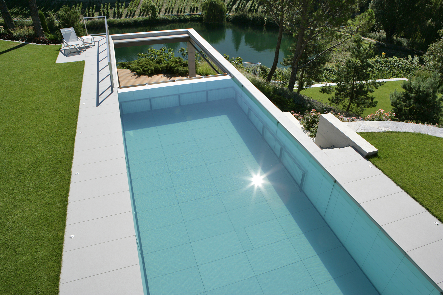 piscine dans son jardin verdoyant installée en Suisse et lauréate des Trophées de la piscine 2018 catégorie Piscine installée à l'étranger