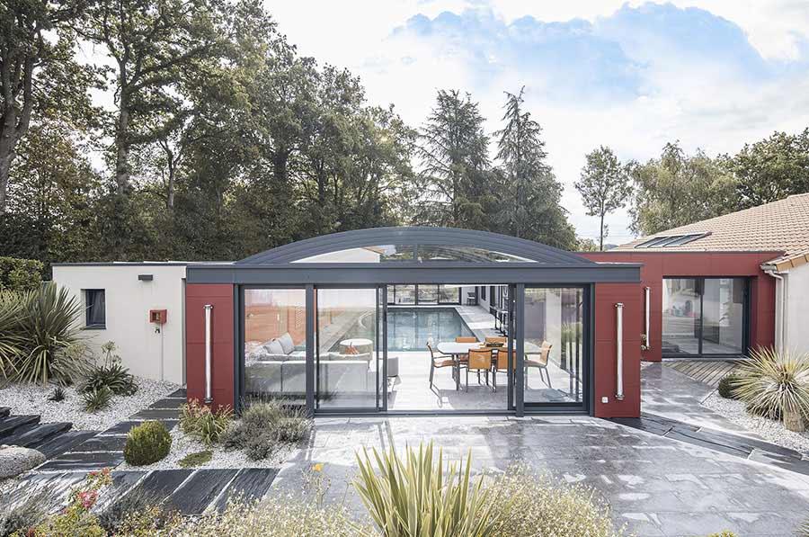 Abri de piscine installée sur une piscine et permettant de prolonger la maison par une véritable pièce de vie en plus