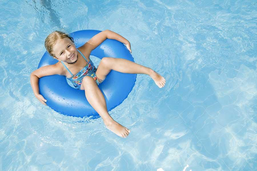 image d'une jeune enfant souriante dans une bouée dans une piscine illustrant l'article