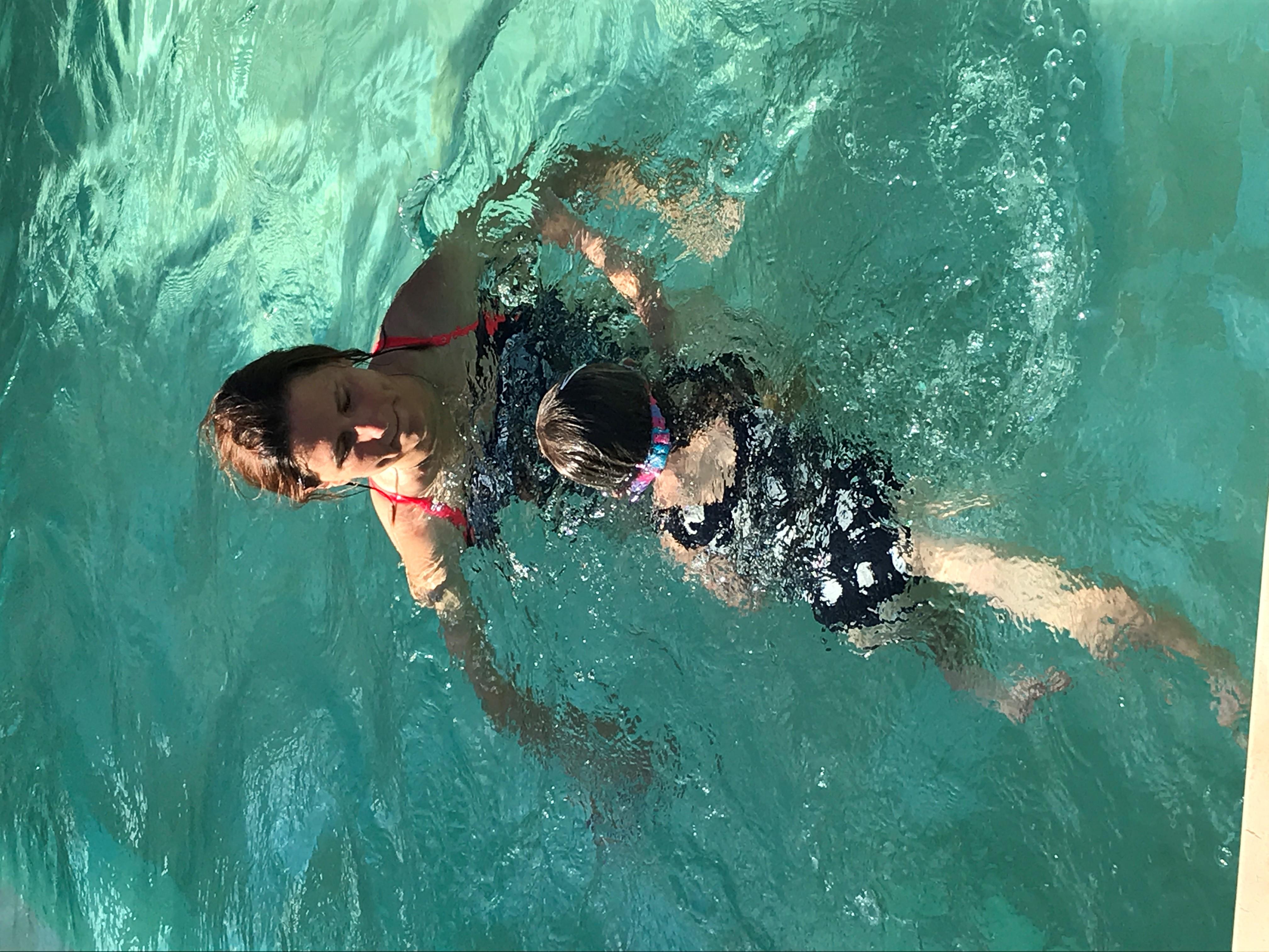 Ministre des sports nageant avec une enfant dans une picine dans le cadre de la première classe bleue dans une piscine privée en juillet 2021